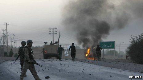 Afghan soldiers walk towards flames outside the U.S. Consulate after an attack by insurgents, in Herat province September 13, 2013