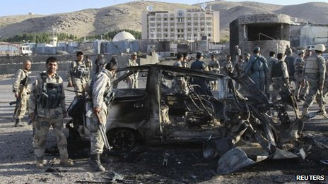 Afghan security forces inspect a damaged car, which was used during a suicide bomb attack, outside the U.S. consulate in Herat province September 13, 2013