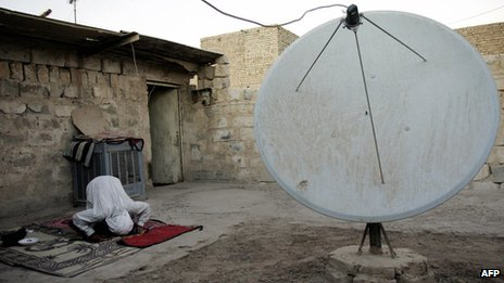 A man prays next to a satellite dish