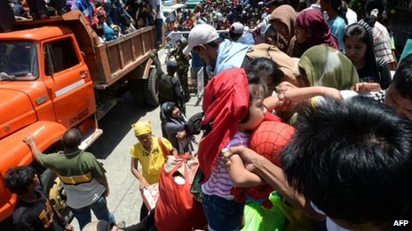 Residents board a truck as they are transported to a safer place after the government enforced a forced evacuation of villagers near the stand-off between government forces and Muslim rebels in Zamboanga City in southern island of Mindanao on 13 September 2013