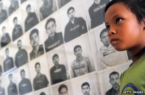 Child looks at photos of Khmer Rouge torture victims
