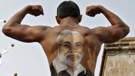 A devotee shows his back, with an image of Gujarat Chief Minister Narendra Modi, as he flexes his muscles
