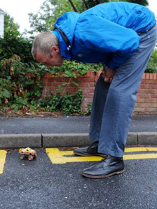 A resident looks at a toy car in the parking space