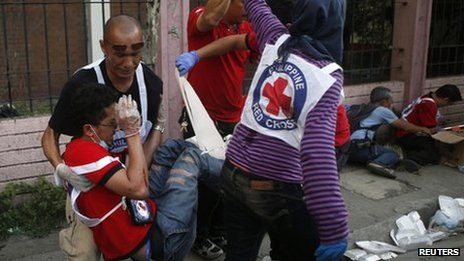 Philippine Red Cross personnel help their wounded colleague after a mortar attack near the scene of fighting between government soldiers and Muslim rebels from the Moro National Liberation Front (MNLF) in Zamboanga city in southern Philippines on 13 September 2013.