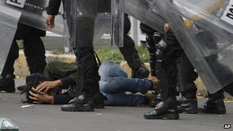 Riot police detain a protester during a mass eviction of striking teachers in Mexico City's main square, 13 September 2013