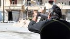 A Syrian soldier takes aim at rebel fighters positioned in the mountains of the Christian town of Maaloula on 13 September