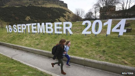 Children running alongside sign showing referendum date