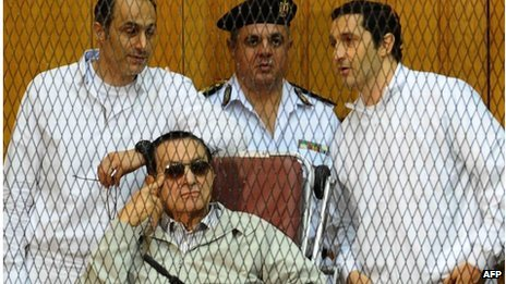 Hosni Mubarak and his two sons Alaa (R) and Gamal stand behind bars during their trial at the Police Academy on 14 September