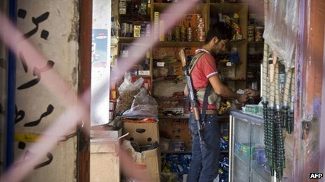 A rebel fighter buys a chocolate bar from a store in the outskirts of Saraqib, southwest of Syrian city of Aleppo
