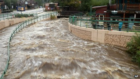 Flood waters rush through downtown Evergreen , Colorado