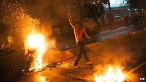 A Cambodia protester walks near flames during a clash with police in Phnom Penh on 15 September 2013