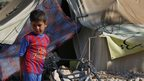 Child stands outside a tent in a refugee camp in Lebanon
