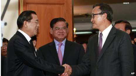 Cambodian Prime Minister Hun Sen, left, shakes hands with opposition party leader Sam Rainsy, right, after a meeting, as Sar Kheng, center, deputy prime minister, looks on at the National Assembly in Phnom Penh, Cambodia, Monday, 16 September 2013
