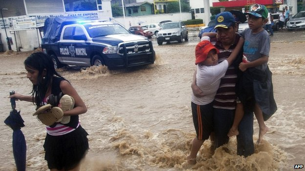 A family wades through a flooded street in Acapulco, Guerrero state, following the passage of Tropical Storm Manuel on 15 September, 2013.