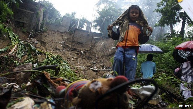 A boy stands in a neighbourhood where several people were killed after a house collapsed in a landslide in Acapulco on 15 September, 2013.