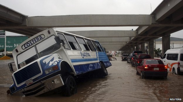 A stranded bus is seen as cars make their way through a flooded street in Acapulco on 15 September, 2013