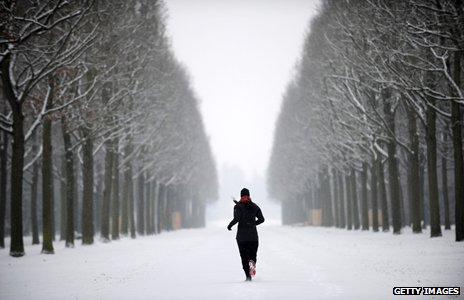 Jogger runs through snowy forest
