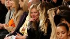 Model Kate Moss (centre) watches the Unique Spring/Summer 2014 fashion show on day three of London Fashion Week at the Topshop Show Space, London