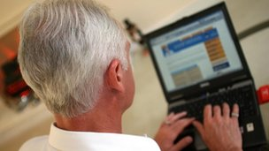 A man with grey hair using a laptop