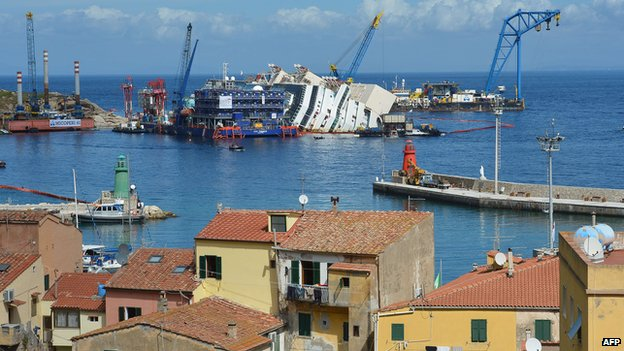 A general view shows houses in Giglio Porto as the Costa Concordia cruise ship wreck begins to emerge from water on 16 September 2013.