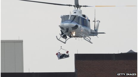 A person is carried by helicopter away from the navy building