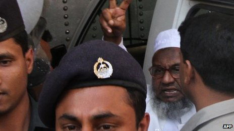 In this photograph taken on 5 February 2013, Abdul Kader Mullah gestures as he walks with officials at the central jail in Dhaka