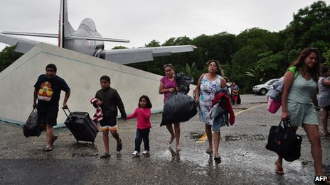 Mexican tourists arrive at the Mexican Navy headquarters after being trapped by heavy rains in Acapulco on 17 September 2013