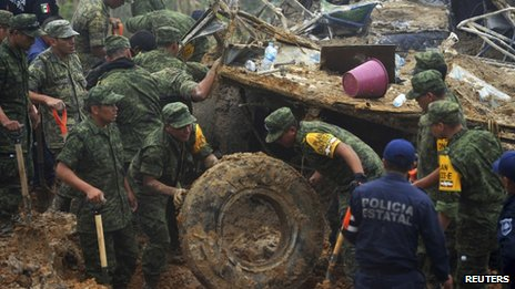 Soldiers and police work around the wreckage of a bus after it was buried by a mountain landslide at Altotonga on 16 September, 2013