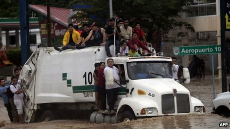 Residents attempt to leave the flooded area in Acapulco after heavy rains hit the area on 16 September, 2013.
