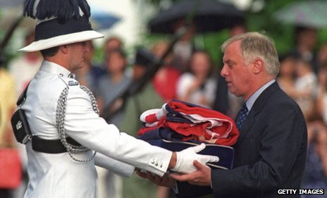 Lord Patten receives the Union Jack flag after it was lowered for the last time at Government House in Hong Kong