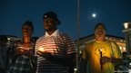 People hold candles in remembrance of people affected by gun violence during a vigil at Freedom Plaza