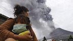 A mother holds her child as Mount Sinabung spews ash and hot lava during an eruption in Perteguhan village in Karo district, Indonesia's north Sumatra province, 17 September, 2013.