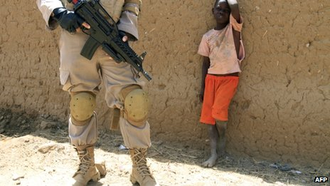 A young boy watches a United Nations peacekeeper in the North Darfur state capital of El-Fasher, on 17 June, 2013.