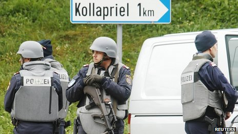 Armed police block the road around the farmhouse