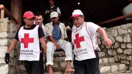 Mexican Red Cross volunteers carry a man during floods in Acapulco on 17 September, 2013