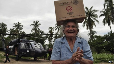 Residents help to unload humanitarian aid from a Black Hawk helicopter at the Pie de La Cuesta military base in Acapulco on 17 September, 2013