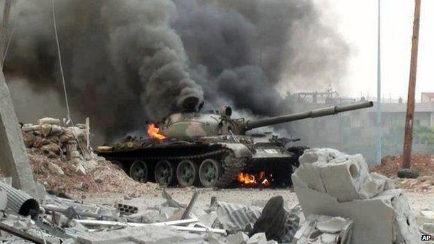 This citizen journalism image provided by The Syrian Revolution against Bashar Assad which has been authenticated based on its contents and other AP reporting, shows a Syrian military tank on fire during clashes with Free Syrian army fighters in Joubar, a suburb of Damascus, Syria, Wednesday, 18 September, 2013.