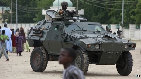 In this photo taken Thursday, Aug. 8, 2013, Nigerian soldiers ride on the armoured tank during Eid al-Fitr celebration in Maiduguri, Nigeria