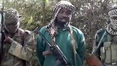 "A picture taken from a video distributed to Nigerian journalists in the country""s north in recent days through intermediaries and obtained by AFP on March 5, 2013 shows Abubakar Shekau (C), the suspected leader of Nigerian Islamist extremist group Boko Haram, flanked by two armed and hooded fighters in an undisclosed place."