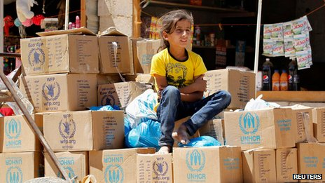Syrian girl sits on aid boxes at the Al Zaatri refugee camp  in Jordan