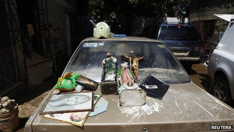 Pictures and religious figurines lie on a car to dry in the flooded Mexican beach resort of Acapulco on 18 September, 2013