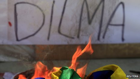 A Brazilian flag burns in front a wall graffiti referring to Brazilian President Dilma Rousseff during a protest on Brazil's Independence Day in Rio de Janeiro on 7 September 2013