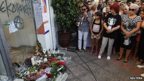 Flowers and mourners at the spot where Pavlos Fyssas was fatally stabbed in Athens