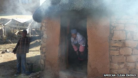 A woman stands in the door of a smoky house in Lesotho
