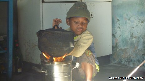 A little boy sits next to a smokeless stove made by African Clean Energy in Lesotho