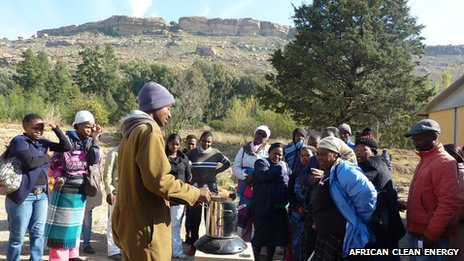 A man demonstrates a smokeless cook stove to a group of potential customers in Lesotho