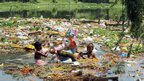 Children salvage reusable materials and offerings from a lake, a day after the immersion of idols of elephant-head Hindu God Ganesha in Bhopal, India, Thursday, Sept. 19, 2013.