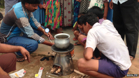 A man demonstrates a smokeless cook stove to a group of potential customers in India
