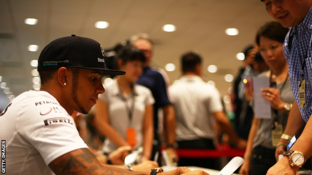 Lewis Hamilton signs autographs for fans in Singapore
