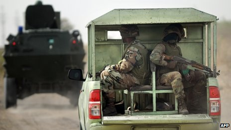 Nigerian soldiers patrol in the north of Borno state close to a Islamist extremist group Boko Haram former camp (June 2013)